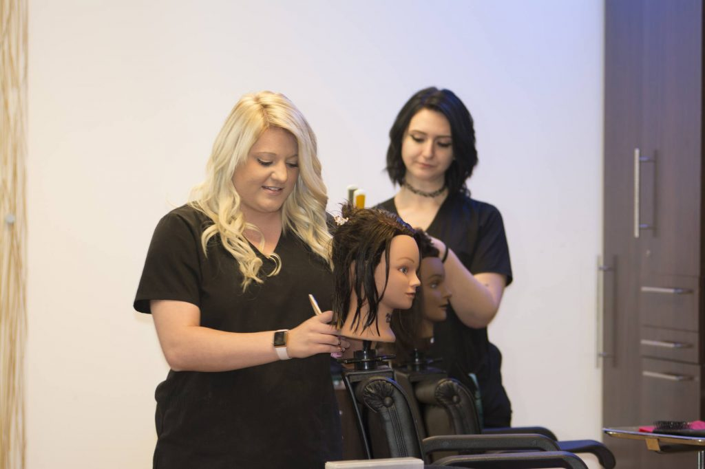 Cosmetology students cutting hair.